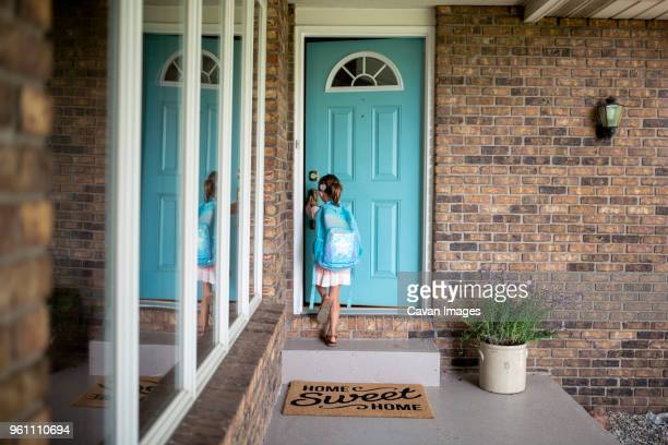 girl with backpack opening door of house - front door stock pictures, royalty-free photos & images