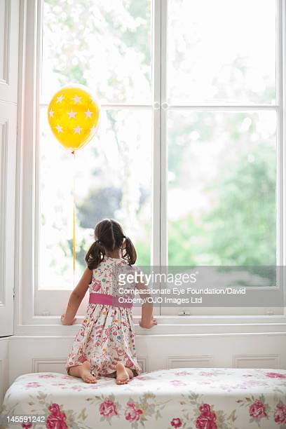Girl with balloon looking out of window, rear view