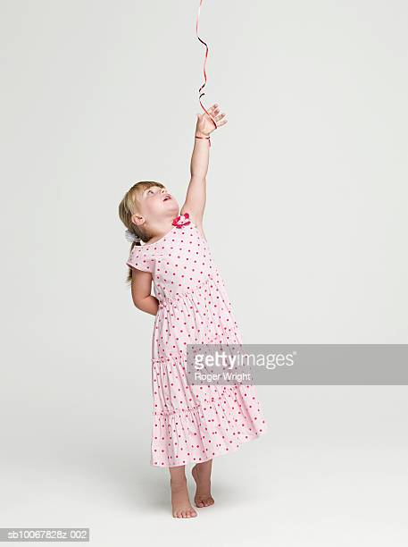 Girl (2-3 years) with balloon string tied to hand, studio shot