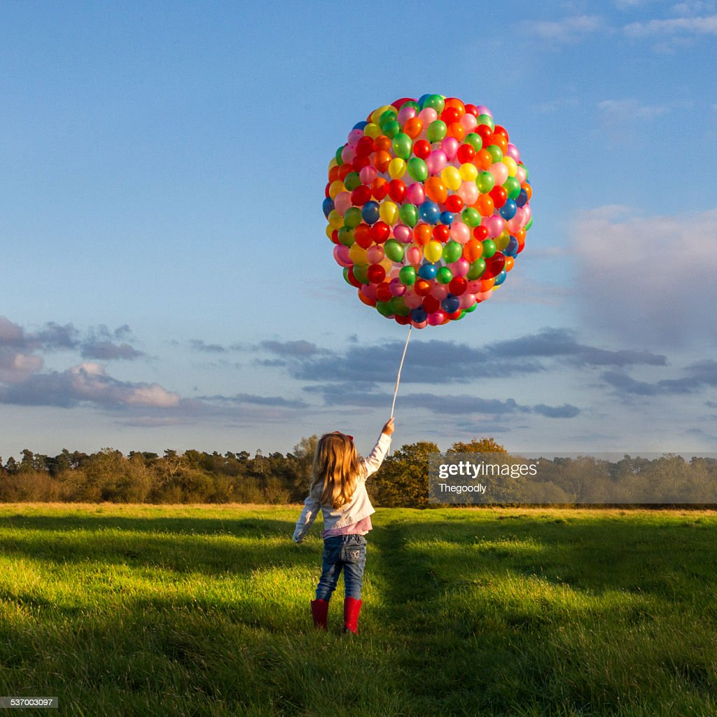 Girl with balloons in meadow : Stock Photo