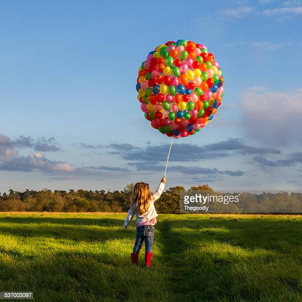 Girl with balloons in meadow
