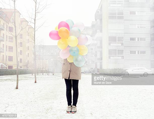 Girl with balloons in mist