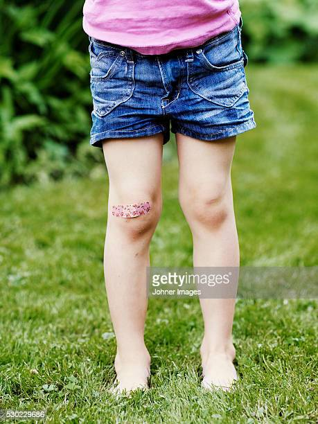 Girl with band-aid on her knee, low section