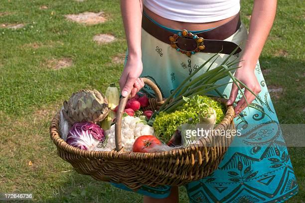 Girl with basket full of vegetables