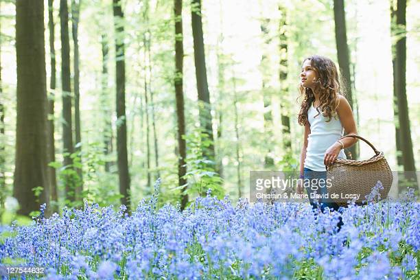 Girl with basket in field of flowers