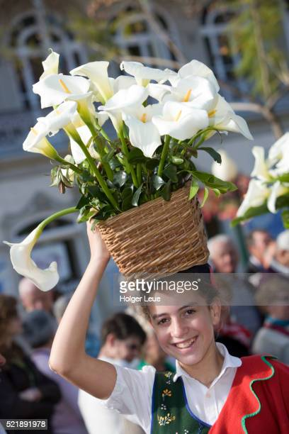 Girl with basket of calla flowers during parade at annual Madeira Flower Festival, Funchal, Madeira, Portugal