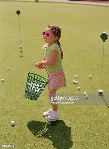Girl with basket of golf balls at driving range