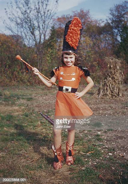 Girl (8-10) with baton, wearing majorette uniform, outdoors, portrait