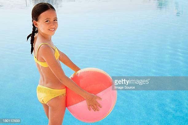 Mädchen mit einem beach ball mit Swimmingpool, Porträt