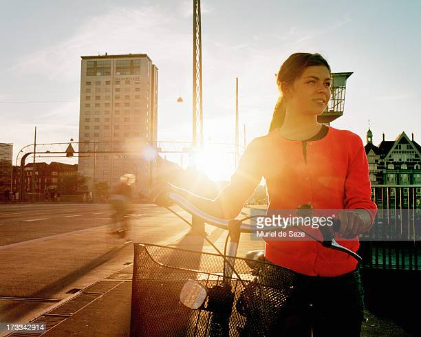 Girl with bicycle by sunset