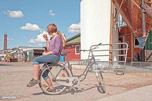 Girl with bicycle eating an apple on farm