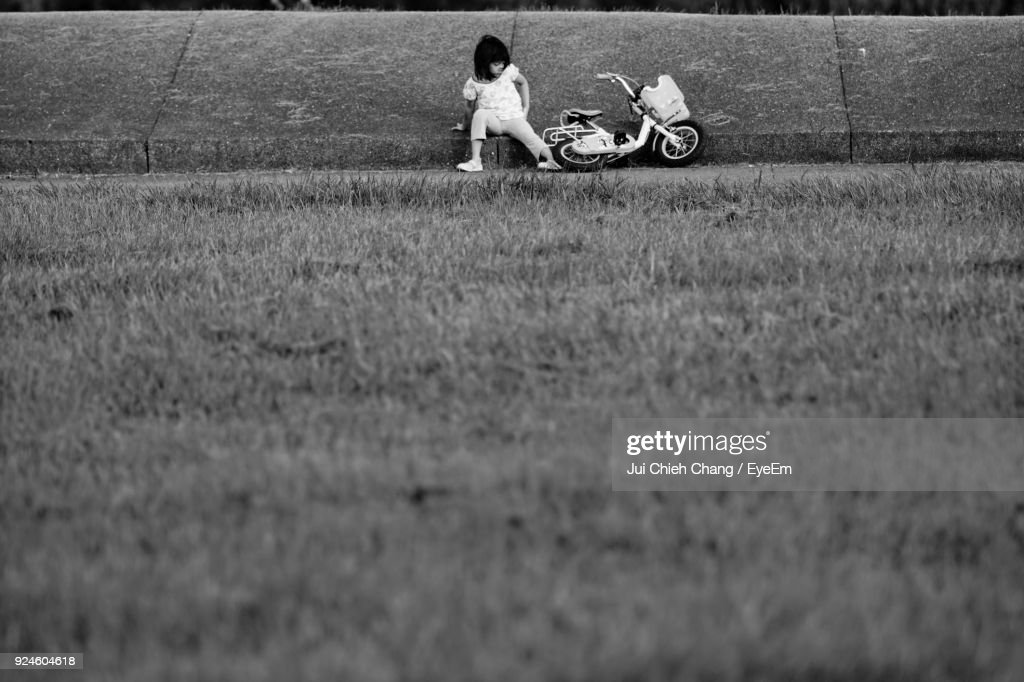 Girl With Bicycle Sitting On Field : Stock Photo