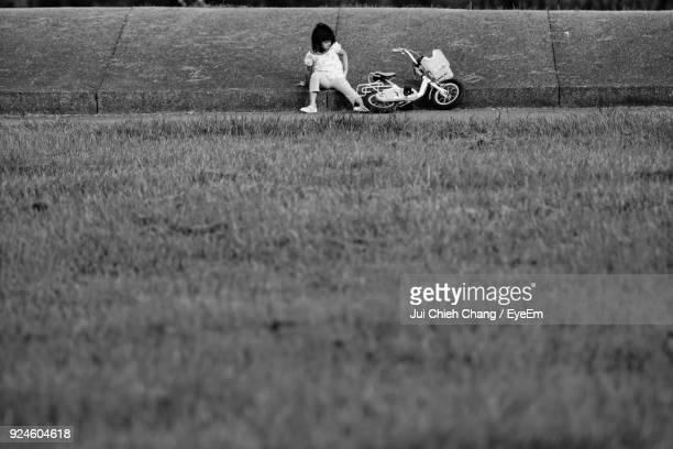 Girl With Bicycle Sitting On Field