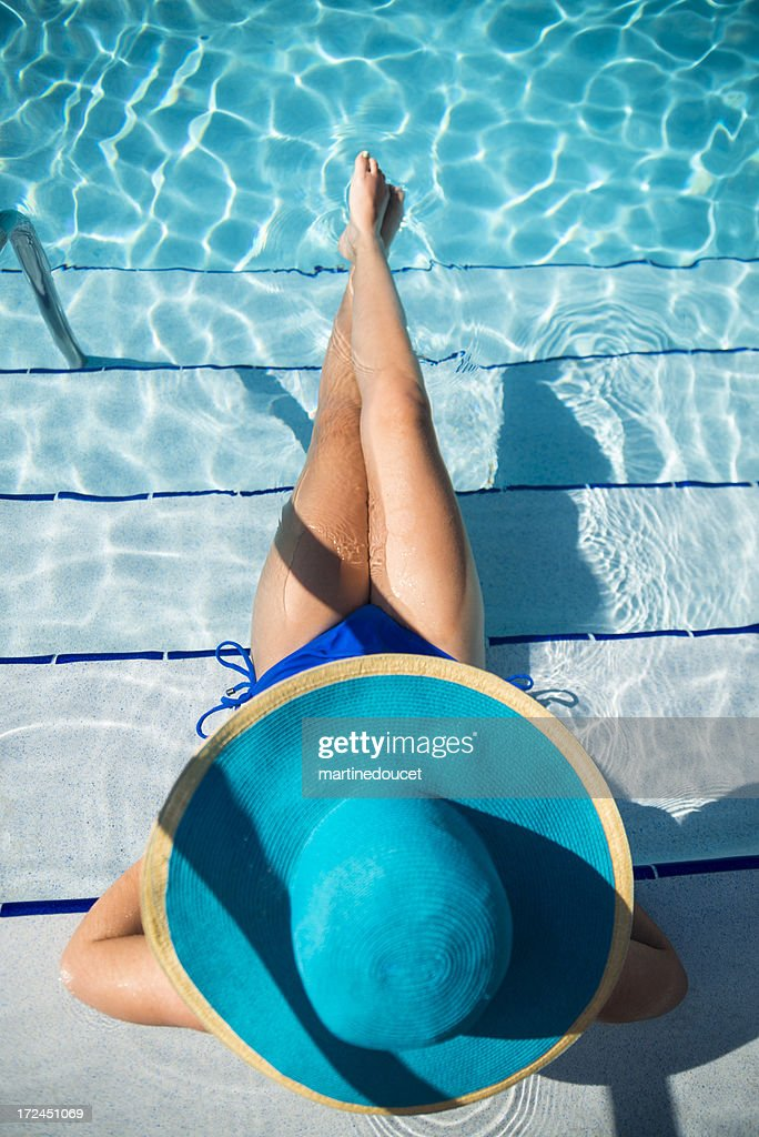 Girl with big blue hat enjoying vacations in pool : Stock Photo