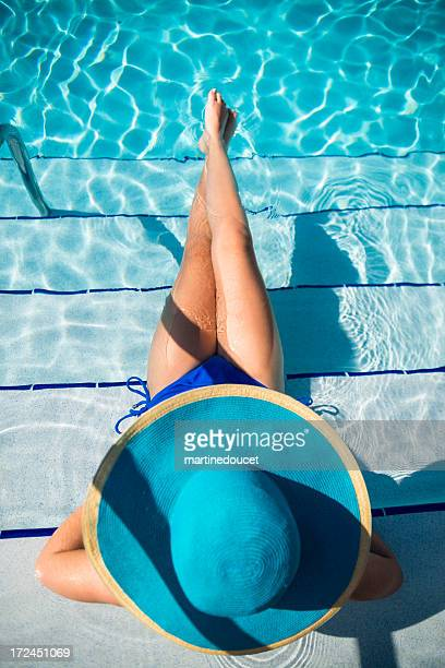 Girl with big blue hat enjoying vacations in pool
