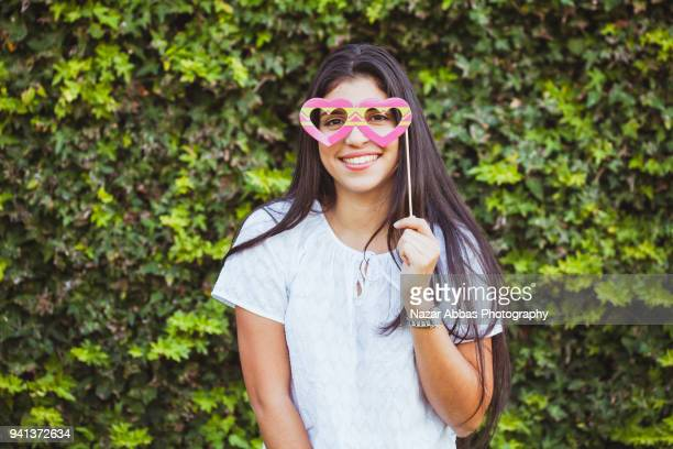 Girl with big smile looking through prop glasses.