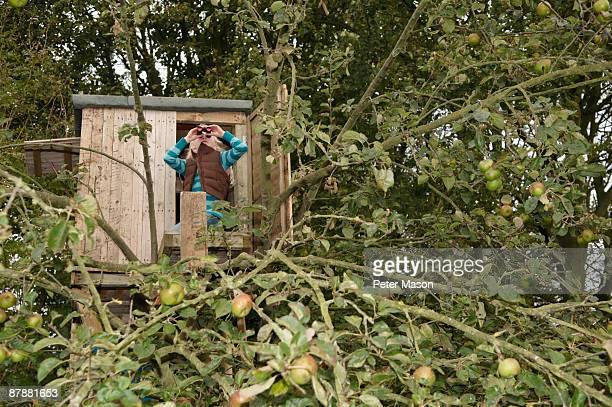 Girl with binoculars in treehouse
