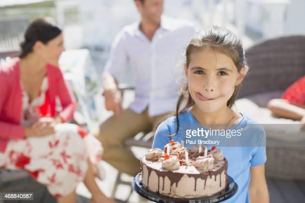 Girl with birthday cake licking lips