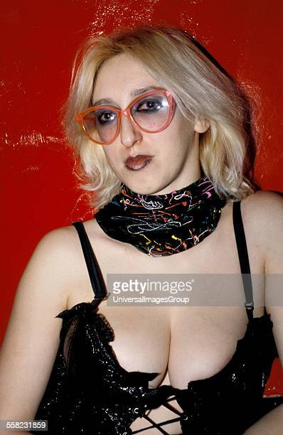 Girl with bleached hair and oversized coloured glasses wearing a pvc corset UK 1980's