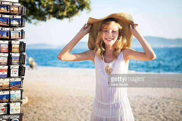 Girl with blond hair next to souvenir shop, trying a sun hat, Zadar, Croatia