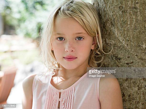 Girl with blonde hair by tree, portrait