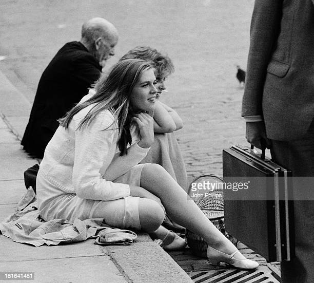 Girl with blonde hair, wearing a summer dress and white cardigan sits on a kerb watching a street performer . Another girl is with her and man sits...