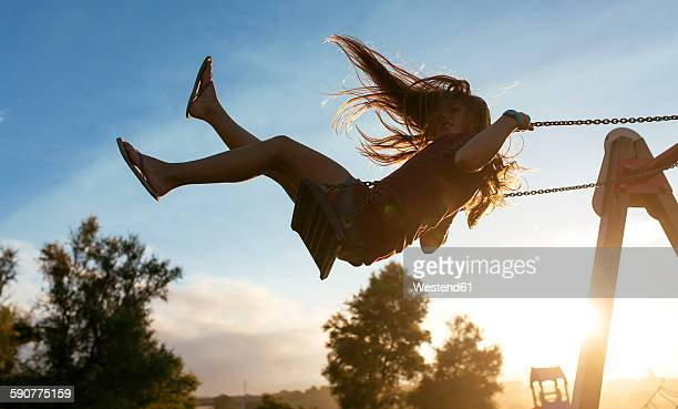Girl with blowing hair on a swing at backlight