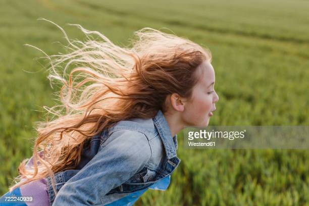 girl with blowing hair running on a field - 吹く ストックフォトと画像