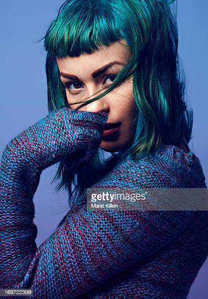 Girl with blue and green hair with hand over mouth