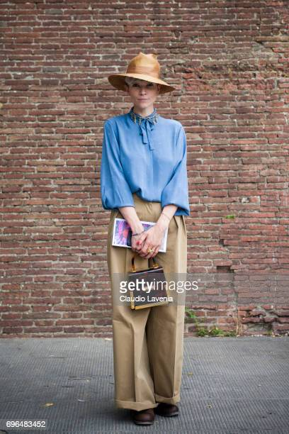Girl with blue blouse and cream pants is seen during Pitti Immagine Uomo 92 at Fortezza Da Basso on June 15 2017 in Florence Italy