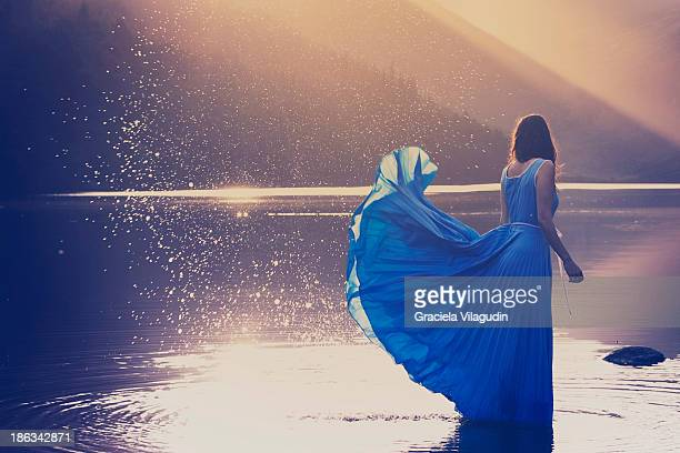 Girl with blue flying dress in a lake