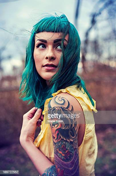 girl with blue hair and tattoos looking over - tattoo stock pictures, royalty-free photos & images