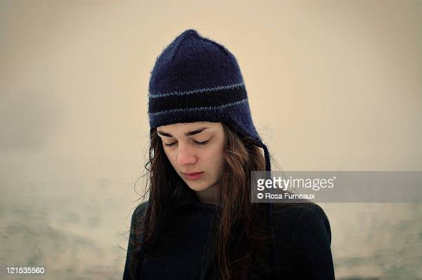 girl with blue hat in snow with eyes closed - ニット帽 ストックフォトと画像