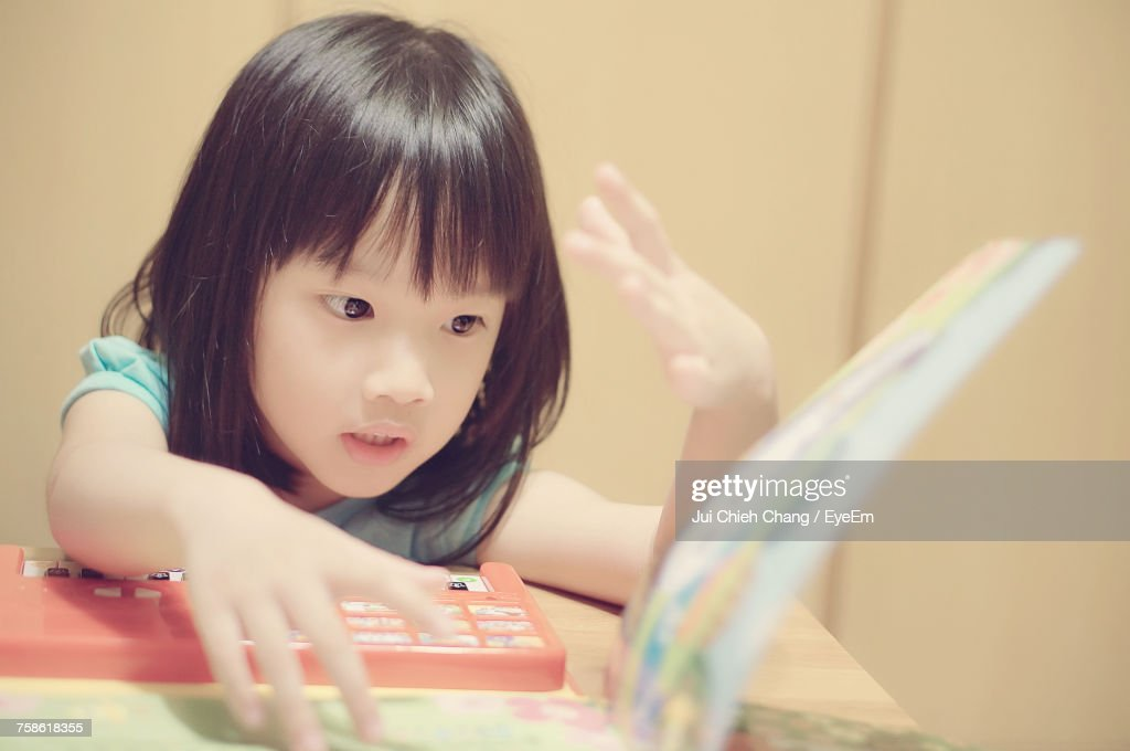 Girl With Book And Toy Sitting At Table : Stock Photo