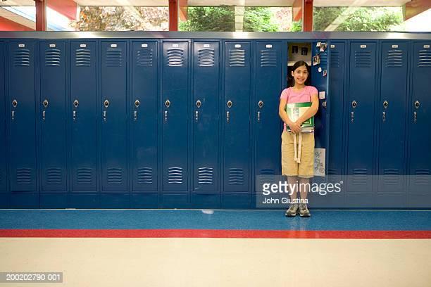 girl (10-12) with books in front of open locker, portrait - ロッカー ストックフォトと画像