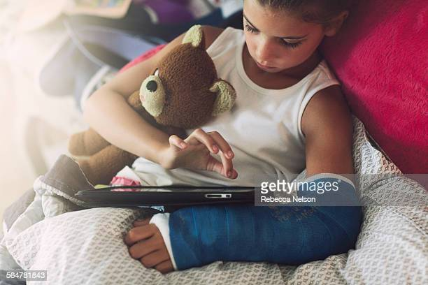 girl, with broken arm, using tablet in bed