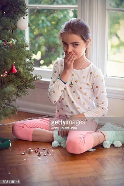 Girl (10-12) with broken christmas ornament