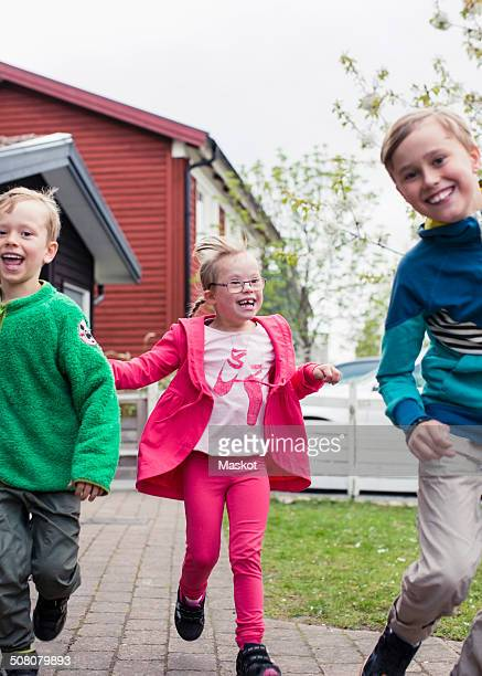 Girl with brothers running in lawn