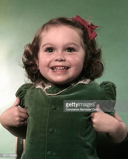 A girl with brown curls wearing a green dress 1st October 1954