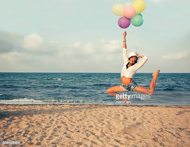 Girl with bunch of balloons jumping at the beach