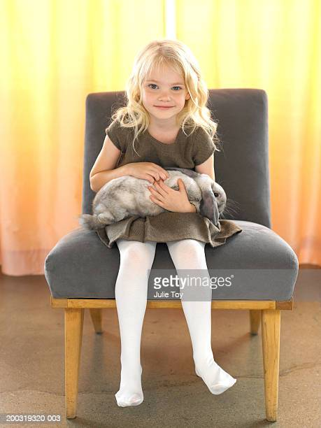 Girl (4-6) with bunny sitting on chair