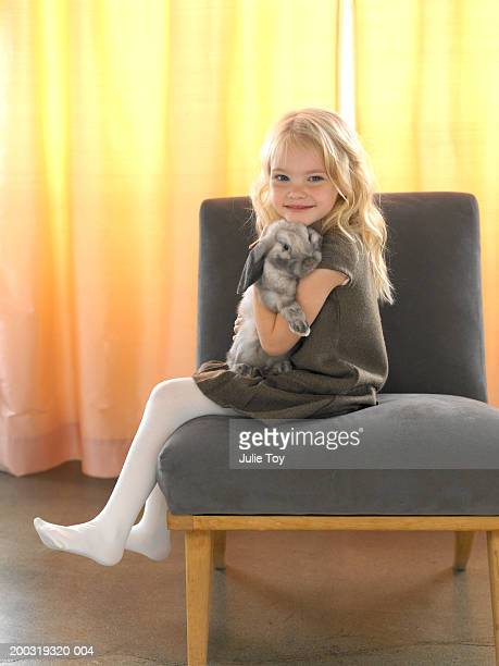 girl (4-6) with bunny sitting on chair - little girls in pantyhose stock pictures, royalty-free photos & images