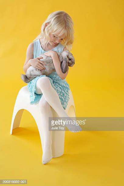 girl (4-6) with bunny sitting on platic chair - children pantyhose stock photos and pictures