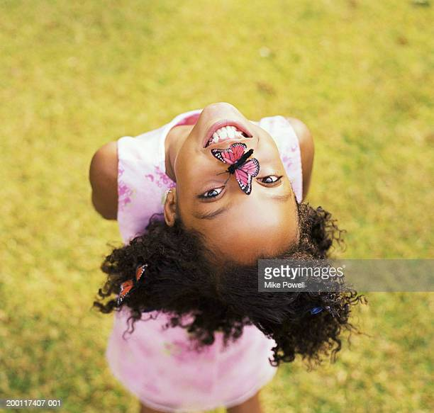 Girl (8-10) with butterfly on nose, hanging head upside down, portrait