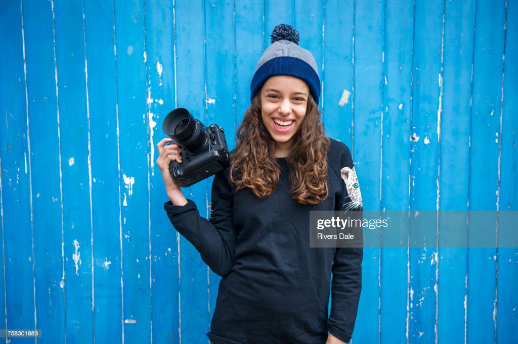 Girl with camera against blue wooden panelling background : Stock Photo