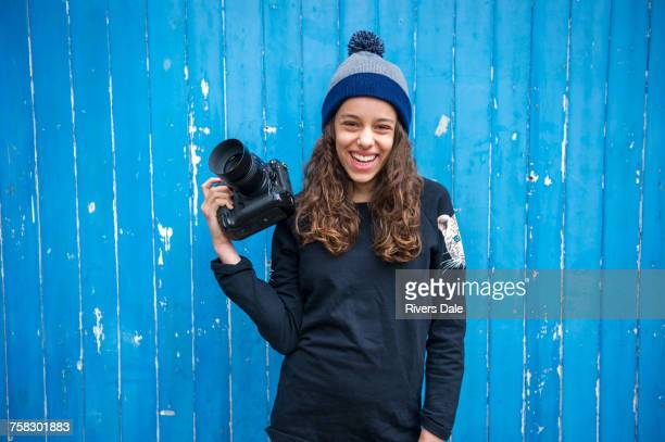 Girl with camera against blue wooden panelling background