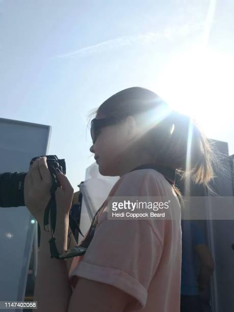 girl with camera and ray of light - heidi coppock beard stock-fotos und bilder