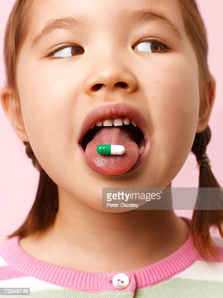 Girl (6-7) with capsule on tongue, looking to side, close-up