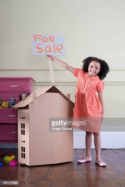 Girl with cardboard house and for sale sign