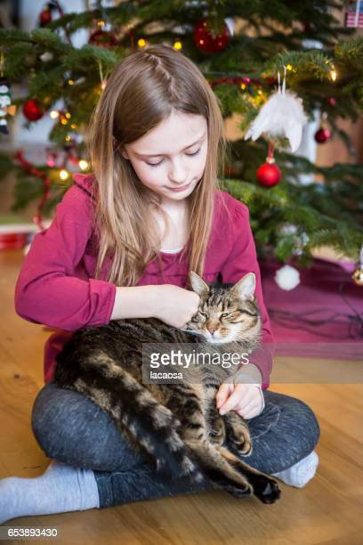 girl with cat in front of a christmas tree
